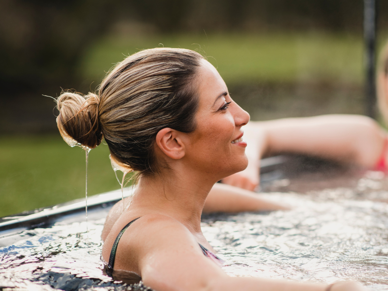 Lady enjoying spa outside - Oasis Pools have New Zealand Made Custom Kiwi Spa Pools in different colours